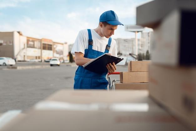 Doręczyciel w jednolitych paczkach czekowych, usługa dostawy. mężczyzna stojący przy kartonowych paczkach w pojeździe, mężczyzna dostawy, kurier lub wysyłka