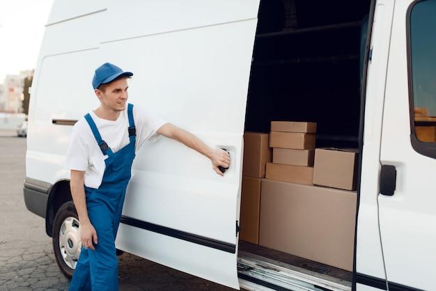 Doręczyciel w jednolitym zamykaniu drzwi samochodowych, auto z paczkami i kartonami, dostawa. mężczyzna stojący przy kartonowych paczkach w pojeździe, mężczyzna dostawy, kurier lub wysyłka