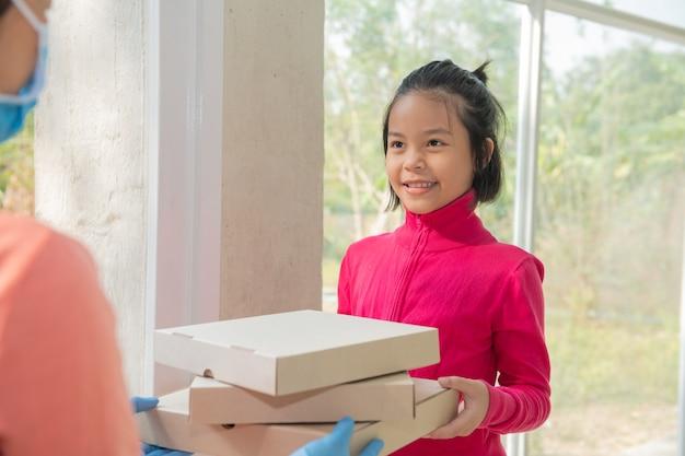 Doręczyciel w koszulce, w masce ochronnej i rękawiczkach podający zamówienie na jedzenie, trzymający przed domem trzy pudełka po pizzy, kobieta przyjmująca dostawę pudełek od dostawcy podczas epidemii covid-19.