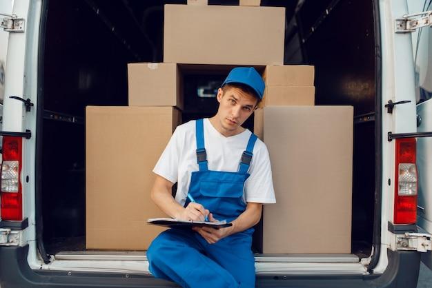 Doręczyciel w mundurze, paczki w samochodzie, ładunek, dostawa. mężczyzna stojący przy kartonowych paczkach w pojeździe, mężczyzna dostawy, kurier lub wysyłka
