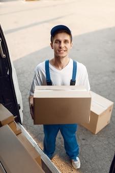 Doręczyciel w mundurze rozładowuje samochód z paczkami, firma kurierska. mężczyzna stojący przy kartonowych paczkach w pojeździe, mężczyzna dostawy, kurier lub wysyłka