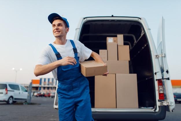 Doręczyciel w mundurze trzyma paczki w samochodzie, usługi kurierskie, doręczanie. mężczyzna stojący przy kartonowych paczkach w pojeździe, mężczyzna dostawy, kurier lub wysyłka