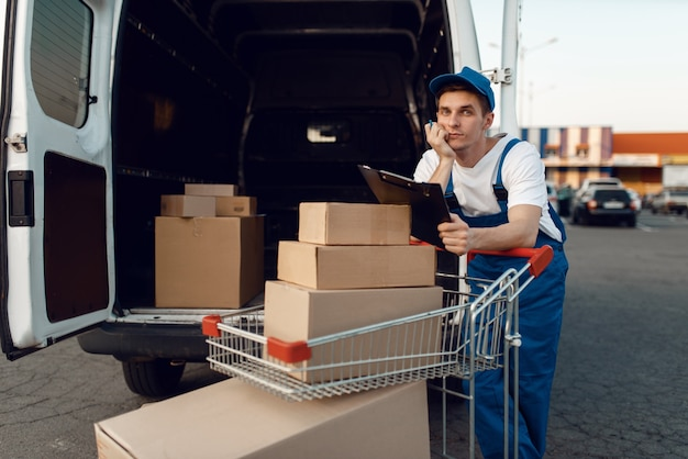 Doręczyciel w mundurze trzyma wózek z pudełkami przy samochodzie z paczkami, firma kurierska. mężczyzna stojący przy kartonowych paczkach w pojeździe, mężczyzna dostawy, kurier lub wysyłka