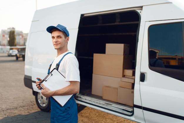 Doręczyciel w mundurze trzymający paczkę i zeszyt, kartony w samochodzie, kurier. mężczyzna stojący przy kartonowych paczkach w pojeździe, mężczyzna dostawy, kurier lub wysyłka