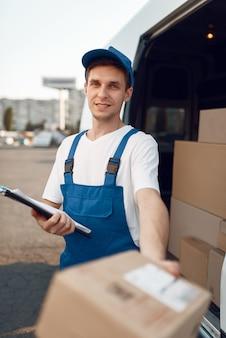 Doręczyciel w mundurze wydaje paczkę, kartony w samochodzie, usługę dostawy. mężczyzna stojący przy kartonowych paczkach w pojeździe, mężczyzna dostawy, kurier lub wysyłka