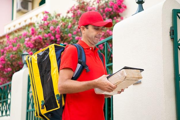 Doręczyciel w średnim wieku trzymający schowek i pudełko kartonowe oraz czytający adres na paragonie. skupiony listonosz w czerwonym mundurze, niosący torbę termiczną i dostarczający zamówienie. dostawa do domu i koncepcja poczty