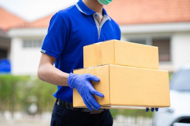 Doręczyciel włożył rękawiczki i maski do przechowywania kartonów