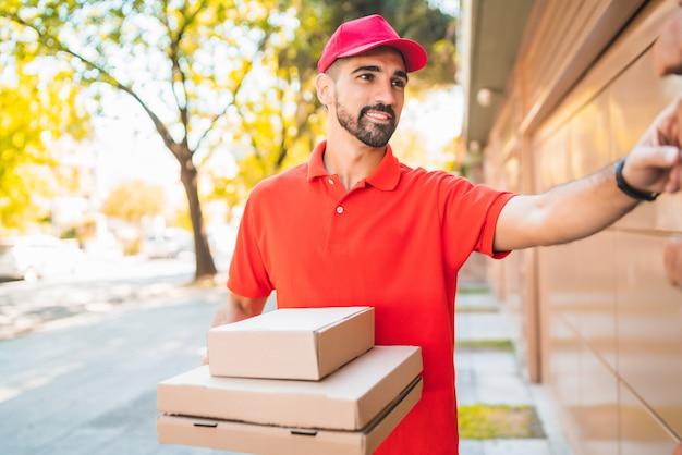 Doręczyciel z pudełkiem po pizzy dzwoni do drzwi domu.