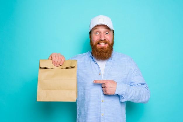 Doręczyciel ze szczęśliwym wyrazem twarzy jest gotowy do dostarczenia paczki z jedzeniem