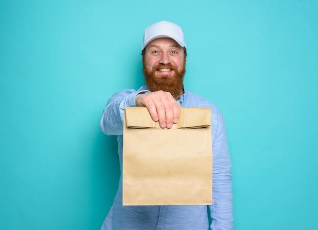 Doręczyciel ze zdumionym wyrazem twarzy gotowy do dostarczenia torby z jedzeniem na niebiesko.