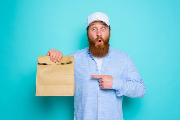 Doręczyciel ze zdziwionym wyrazem twarzy jest gotowy do dostarczenia paczki z jedzeniem
