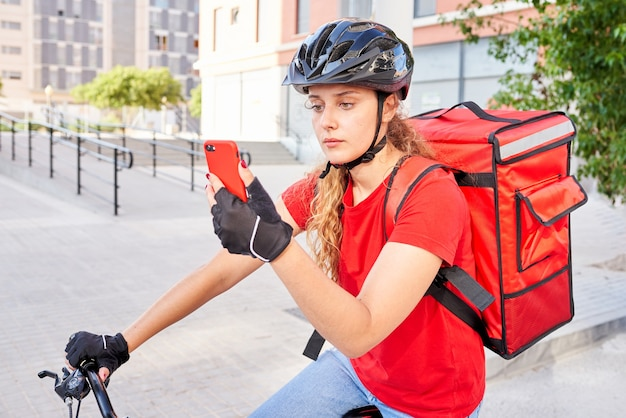 Doręczycielka rowerzystka sprawdza za pomocą telefonu komórkowego adres swojej następnej przesyłki