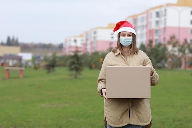 Doręczycielka w czerwonej czapce świętego mikołaja i medycznej masce ochronnej trzyma duże pudełko na zewnątrz
