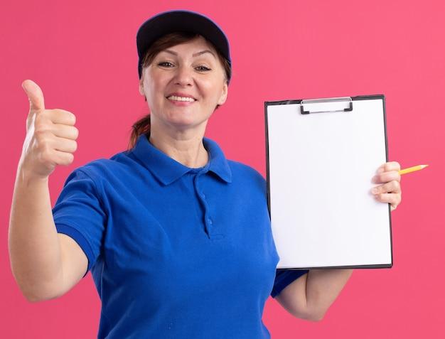 Doręczycielka w średnim wieku w niebieskim mundurze i czapce trzymająca notatnik z pustymi stronami, patrząc na przód, uśmiechnięta wesoło, pokazująca kciuki do góry, stojąca nad różową ścianą