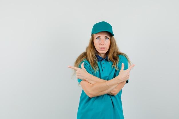 Doręczycielka w t-shircie, z czapką skierowaną w bok, krzyżując ramiona i wyglądająca rozsądnie