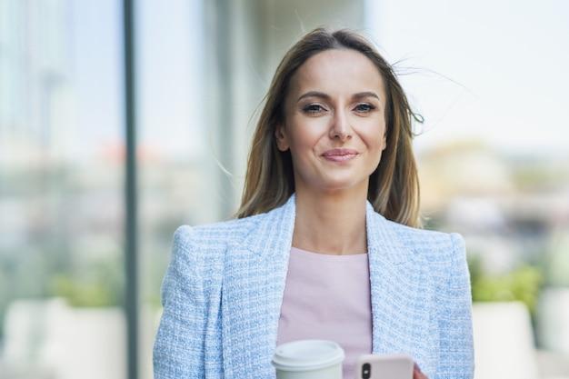 Dorosła atrakcyjna biznesowa kobieta z smartphone i kawy spaceru po mieście. zdjęcie wysokiej jakości