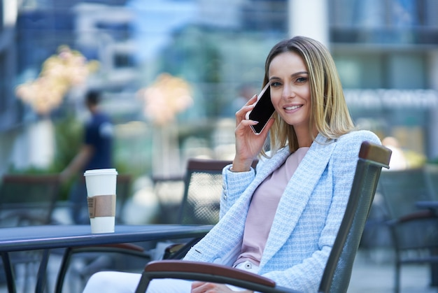 Dorosła atrakcyjna kobieta korzystająca ze smartfona i relaksująca się w mieście