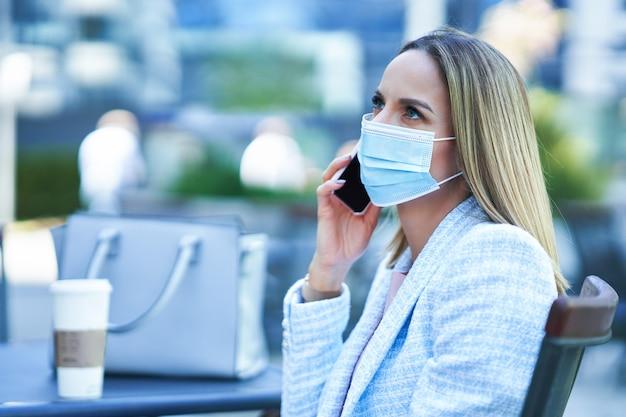Dorosła atrakcyjna kobieta w masce korzystająca ze smartfona i relaksująca się w mieście