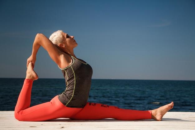 Dorosła blond kobieta z krótką fryzurą ćwiczy jogę na molo na tle niebieskiego nieba i morza