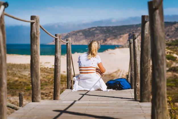 Dorosła blond turystka siedząca na ścieżce prowadzącej do plaży praia do guincho.