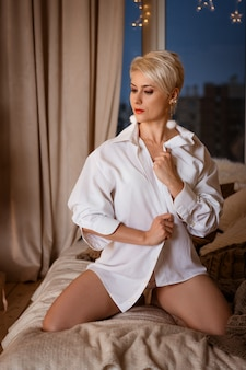 Dorosła blondynka pozowanie wieczorem w białej koszuli na łóżku