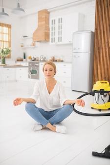 Dorosła blondynka z zamkniętymi oczami siedzi w pozycji lotosu na podłodze w kuchni
