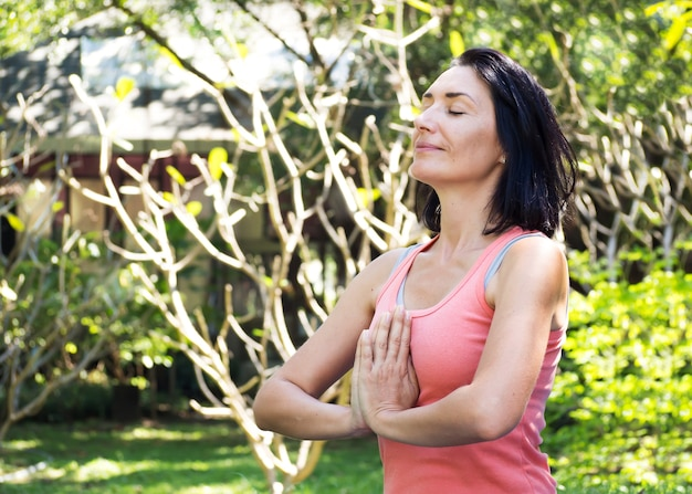 Dorosła caucasian kobieta naciska ręki wpólnie przy klatką piersiową na znak szacunku