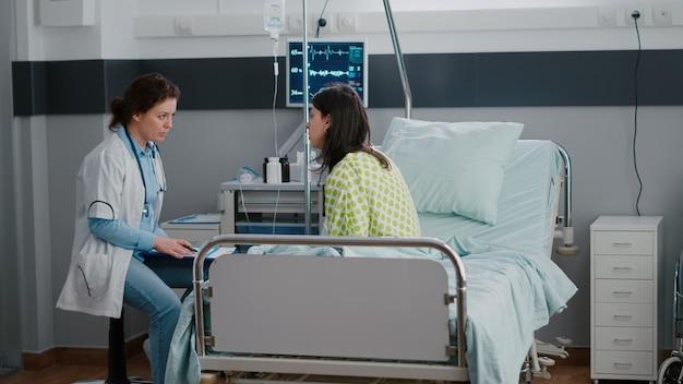 Dorosła chora kobieta siedzi w łóżku, podczas gdy lekarz bada chorobę