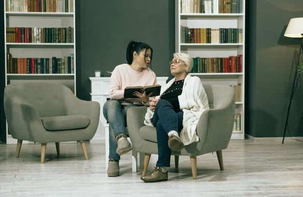 Dorosła córka czytanie książki dla jej starej matki