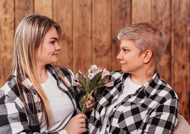 Dorosła córka daje matce kwiaty. patrzymy na siebie