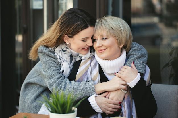 Dorosła córka przytula i całuje swoją starszą matkę, kiedy spotykają się w kawiarni