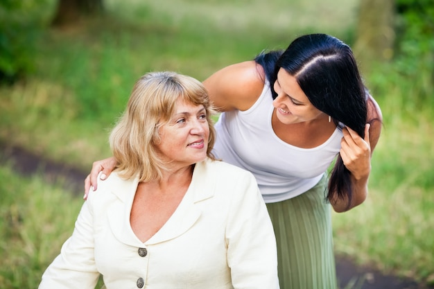 Dorosła córka przytula starszą matkę na zewnątrz w parku