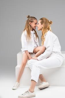 Dorosła długowłosa dziewczyna z kokem pieszcząca nos swojej młodszej siostry podczas sesji zdjęciowej