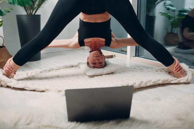 Dorosła dojrzała kobieta robi jogę w domu pokój dzienny z samouczkami online na laptopie