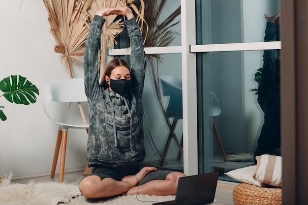 Dorosła dojrzała kobieta robi jogę w domu w salonie z samouczkami online na laptopie