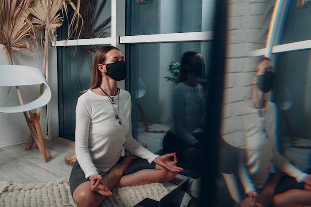 Dorosła dojrzała kobieta w medycznej masce na twarz robi jogę w domu w salonie z samouczkami online na laptopie