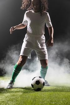 Dorosła dysponowana kobieta bawić się piłkę nożną