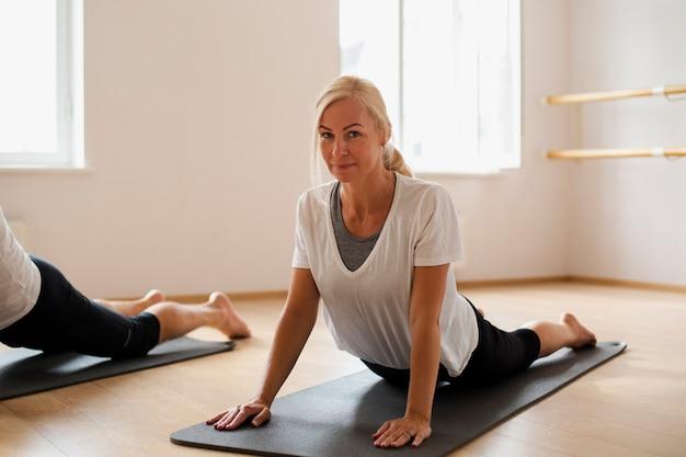 Dorosła dysponowana kobieta ćwiczy joga