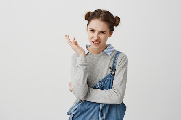 Dorosła dziewczyna 30s gestykuluje sceptycznie wyrażając sprzeciw wobec mimiki. pracodawca z dziecinną fryzurą rozczarowany końcowymi wynikami. reakcje, koncepcja postawy