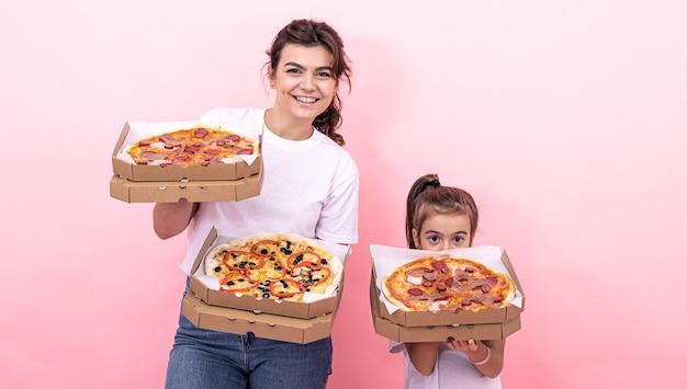 Dorosła dziewczyna i mała dziewczynka z pudełkami pizzy na różowym tle
