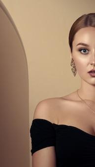 Dorosła dziewczyna ubrana w złoty zestaw biżuterii inspirowany naturą i czarną sukienkę, oparta w beżowym pokoju