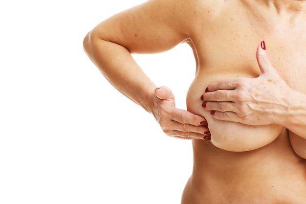 Dorosła kobieta bada piersi na białym tle