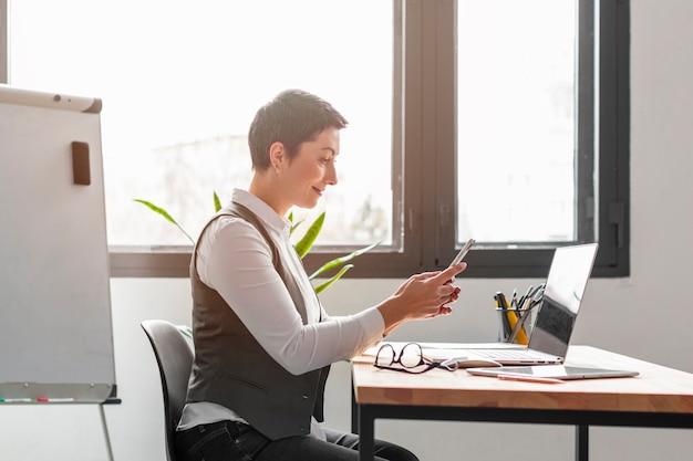 Dorosła kobieta cieszy się pracować przy biurem