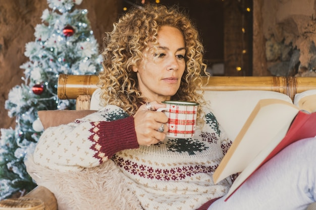 Dorosła kobieta czyta książkę podczas świąt bożego narodzenia w domu