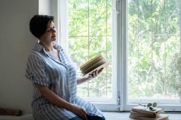 Dorosła kobieta czyta książkę w oknie i uśmiecha się.