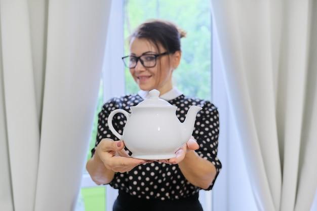 Dorosła kobieta gospodyni domowa z czajnikiem, kobieta trzyma w rękach biały porcelanowy czajnik