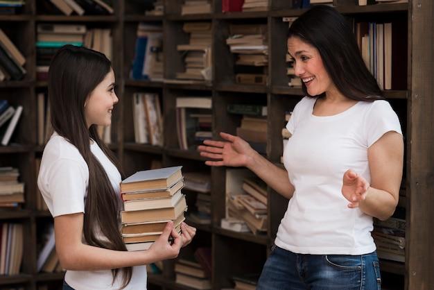 Dorosła kobieta i młoda dziewczyna przy biblioteką