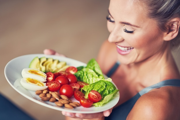 Dorosła kobieta je zdrowy lunch i siedzi na macie do jogi