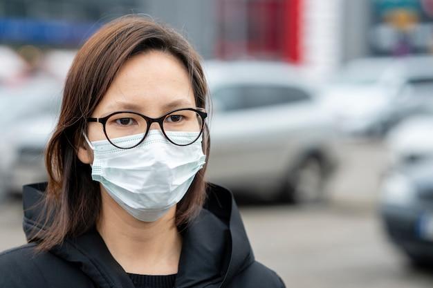 Dorosła kobieta jest ubranym chirurgicznie maskę plenerową