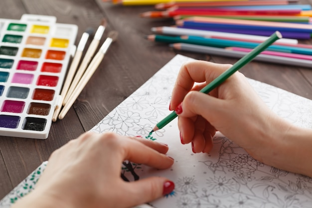 Dorosła kobieta łagodzi stres, malując kolorowankę dla relaksu